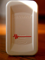 Stetzerizer filters by Stetzer electric front view of dirty power filter. The electrical pollution filter has the STETZERiZER name and logo, as well as the Graham Stetzer red frequency logo. The filter is rectangular, white plastic heavy duty.